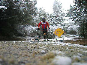 Person with bike standing on snowy road